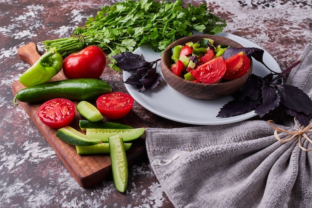 Groentesalade in een houten beker geserveerd met kruiden. Gratis Foto