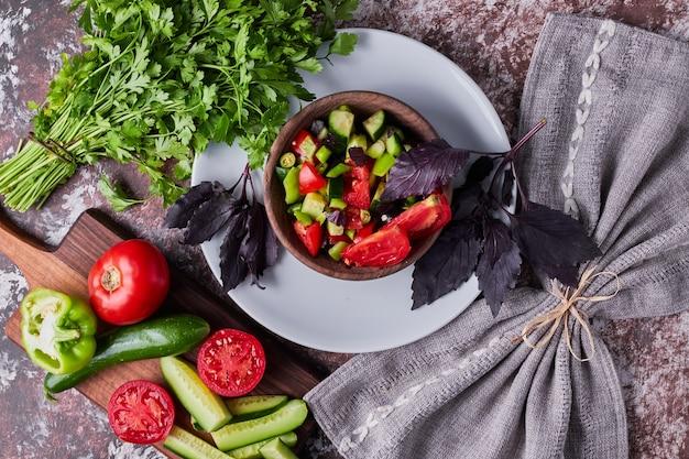Groentesalade in een houten kopje geserveerd met kruiden, bovenaanzicht Gratis Foto