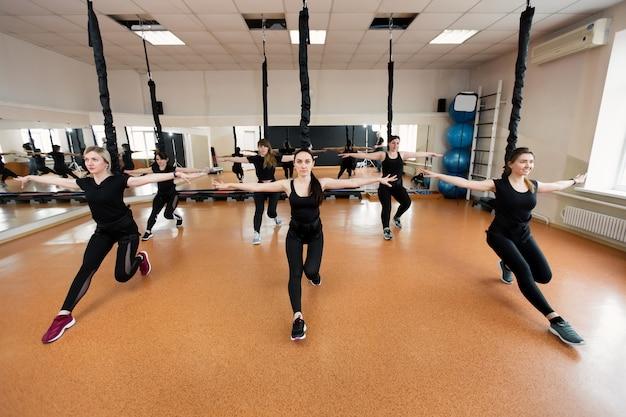 Groep actieve sportmeisjes in zwarte sportkleding houdt zich bezig met parkietfitness in de sportschool. bungeejumpen in de sportschool Premium Foto