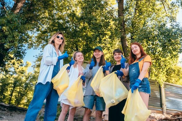 Groep activistenvrienden die plastic afval op het strand verzamelen. jongens tonen hun duim omhoog. Gratis Foto