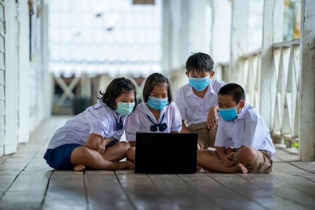Groep aziatische basisschoolleerlingen die een hygiënisch masker dragen om de uitbraak van covid 19 te voorkomen terwijl ze terug naar school gaan, heropenen hun school. Premium Foto