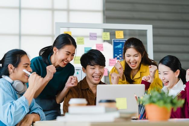 Groep aziatische jonge creatieve mensen in slimme vrijetijdskleding die zaken bespreken vieren het geven van vijf na het omgaan met een gelukkig gevoel en het ondertekenen van een contract of overeenkomst op kantoor. collega teamwerk concept. Gratis Foto