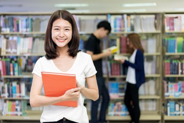 Groep aziatische studenten die samen in bibliotheek bij universiteit bestuderen. Premium Foto