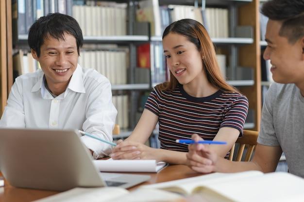 Groep aziatische studenten die voor project in bibliotheek van universiteit onderzoeken. Premium Foto