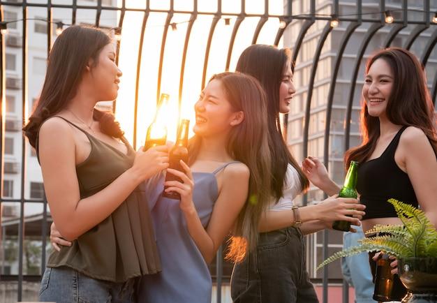 Groep aziatische vriend die en bij terraspartij toejuichen drinken. jongeren die glas met bier roosteren bij restaurant op het dak Premium Foto