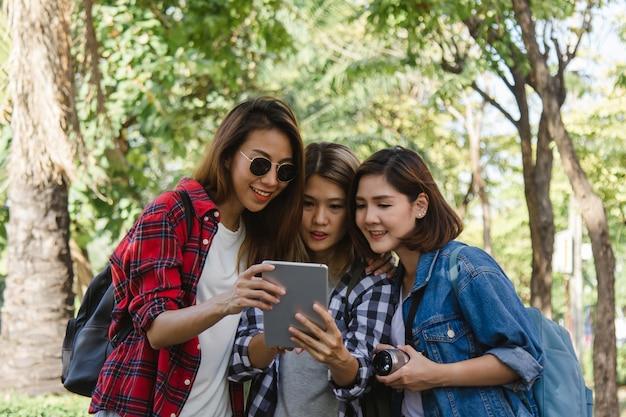 Groep aziatische vrouwen die camera met behulp van om foto te maken terwijl het reizen bij park in stedelijke stad in bangkok Gratis Foto