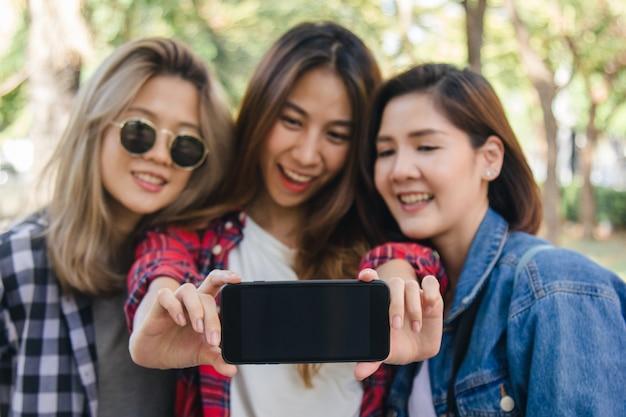 Groep aziatische vrouwen die smartphone gebruiken die selfie terwijl het reizen bij park in stedelijke stad in bangkok nemen Gratis Foto