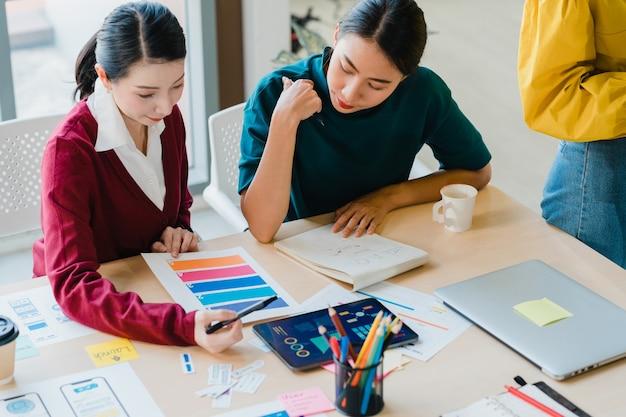 Groep azië jonge creatieve mensen japanse vrouwelijke baas supervisor onderwijs stagiair of nieuwe werknemer spaanse meisje helpt met moeilijke opdracht in het moderne kantoor. collega teamwerk concept. Gratis Foto