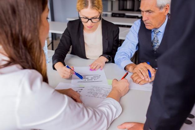 Groep bedrijfsmensen die het businessplan bespreken bij de lijst in het bureau Gratis Foto