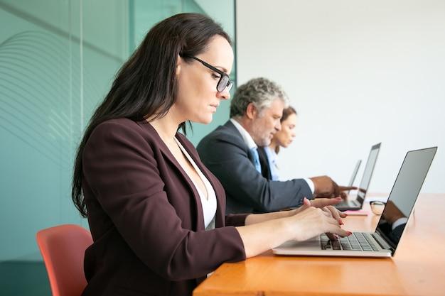 Groep bedrijfsmensen die in lijn zitten en computers in bureau gebruiken. werknemers van verschillende leeftijden typen op laptoptoetsenborden. Gratis Foto