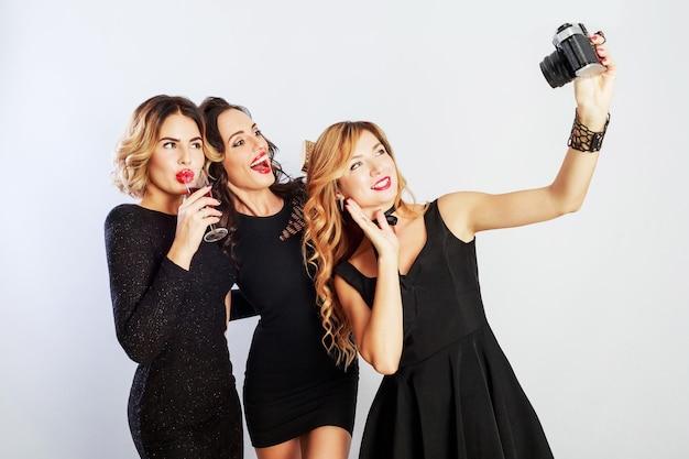 Groep beste vrienden, drie elegante meisjes in zwarte luxe jurk zelfportret maken, rode wijn drinken, die zich voordeed op witte achtergrond. Gratis Foto