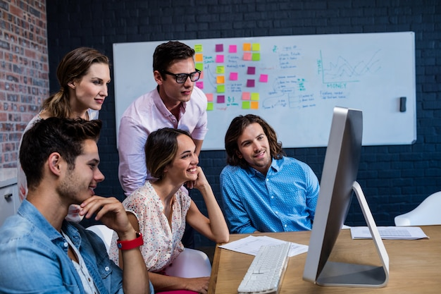 Groep collega's die op een computer letten Premium Foto