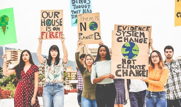 Groep demonstranten op de weg, jongeren uit verschillende culturen en rassen vechten voor klimaatverandering. opwarming van de aarde en milieu concept Premium Foto