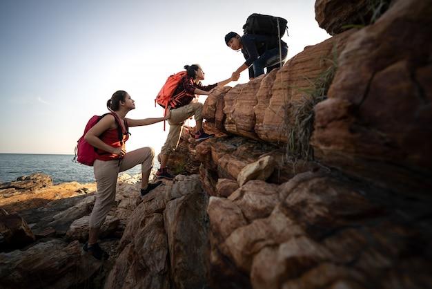 Groep die azië wandelen helpt elkaar silhouet in bergen met zonlicht. Premium Foto