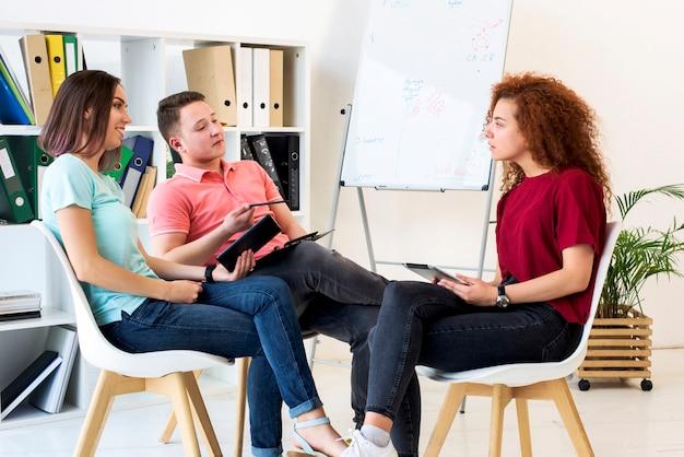 Groep die mensen in studieruimte bespreken terwijl het houden van digitaal tablet en klembord Gratis Foto