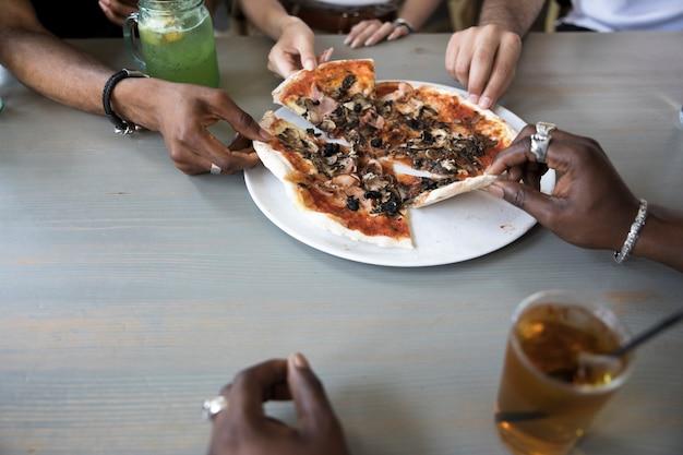 Groep die mensen pizza dicht omhoog eet Gratis Foto