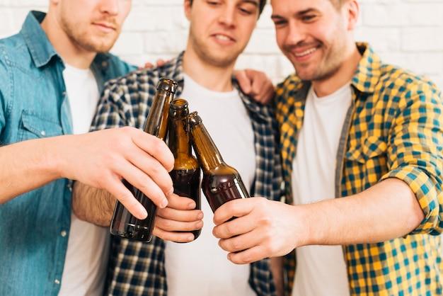 Groep die van drie mannelijke vrienden glimlachen die de bierfles clinking Gratis Foto