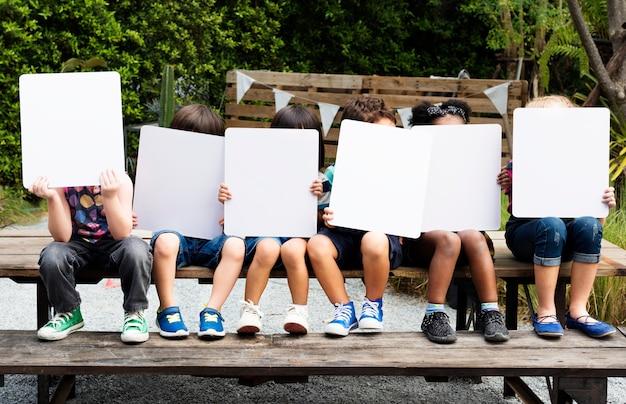 Groep diverse jonge geitjes die aanplakbiljetten houden Premium Foto