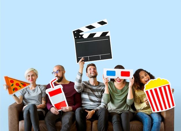 Groep diverse vrienden die film houden emoticons Gratis Foto