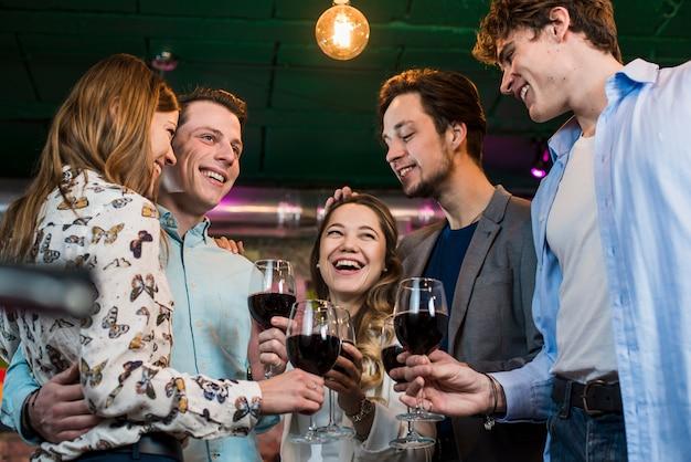 Groep een gelukkige vrienden die avond van dranken in bar genieten Gratis Foto