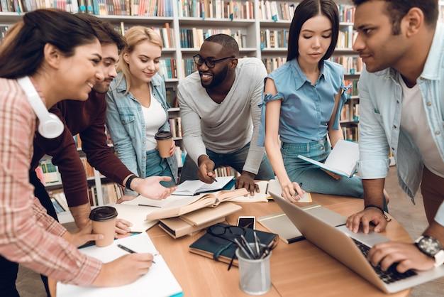 Groep etnische multiculturele studenten die in bibliotheek bespreken Premium Foto