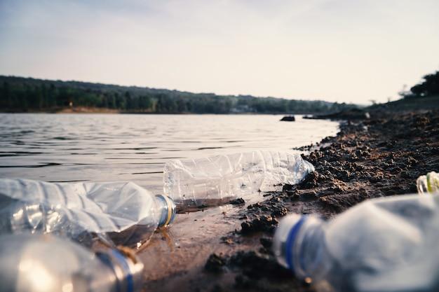 Groep flessenplastiek in de rivier, milieuprobleem en verontreiniging in waterconcept. Premium Foto