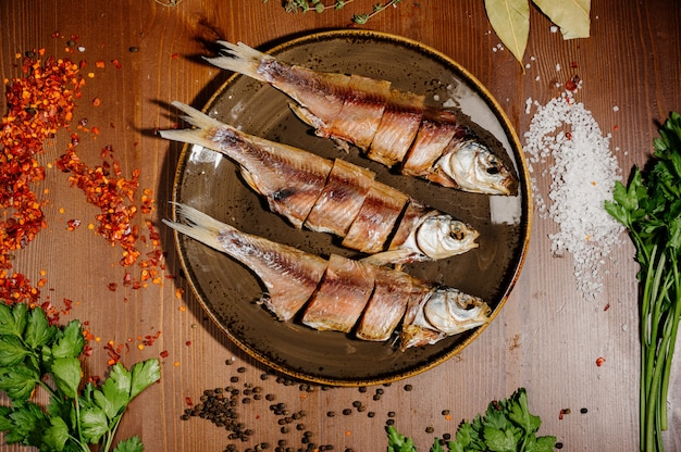 Groep gedroogde vis op plaat. zeevruchten. bovenaanzicht Premium Foto