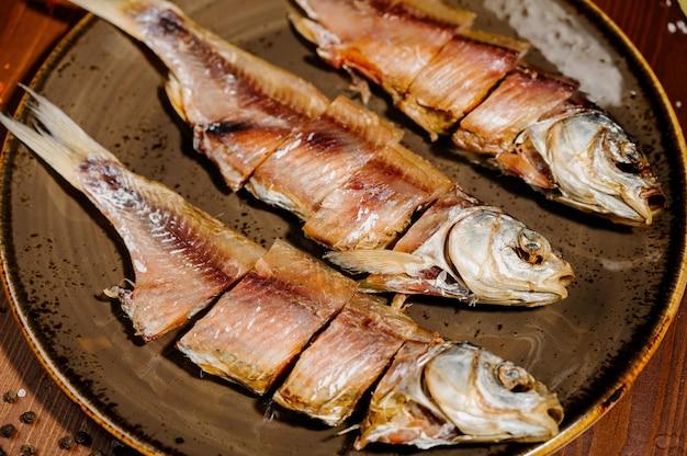 Groep gedroogde vis op plaat. zeevruchten Premium Foto