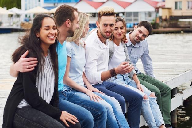 Groep gelukkige jonge vrienden op de pier, plezier in het spelen zorgt voor een emotioneel leven. Gratis Foto