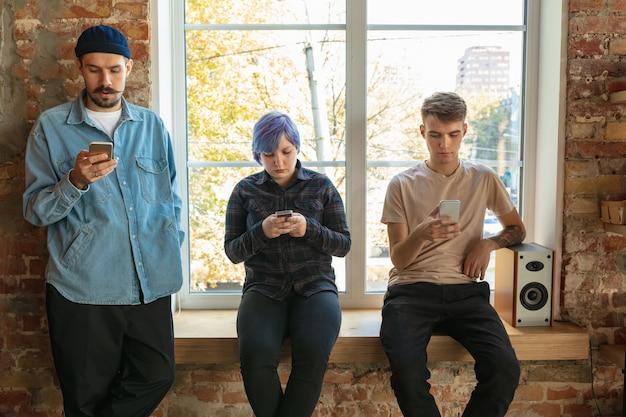 Groep gelukkige kaukasische jonge mensen die zich achter het venster bevinden. nieuws, foto's of video's van smartphones delen, spraak opnemen of games spelen en plezier maken. sociale media, moderne technologieën. Gratis Foto