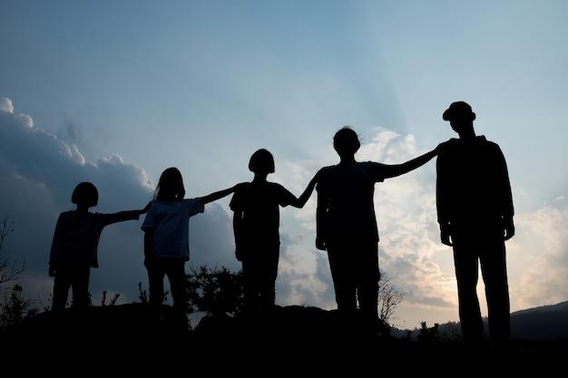 Groep gelukkige kinderen die bij zonsondergang, silhouet spelen Premium Foto