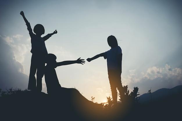 Groep gelukkige kinderen die op de berg bij zonsondergang, silhouet spelen Premium Foto