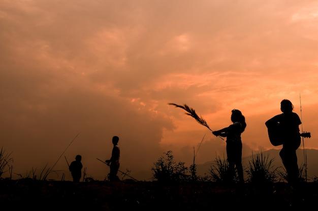 Groep gelukkige kinderen die op weide bij zonsondergang spelen, silhouet Premium Foto