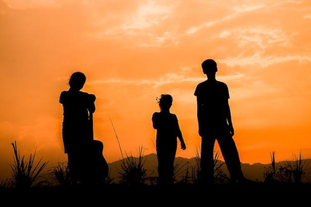 Groep gelukkige kinderen die op weide bij zonsondergang spelen Premium Foto