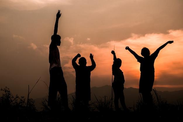Groep gelukkige kinderen die op weide spelen bij zonsondergang, silhouet Premium Foto