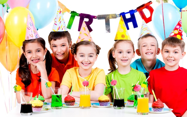 Groep gelukkige kinderen in kleurrijke shirts met plezier op het verjaardagsfeestje - geïsoleerd op een witte. Gratis Foto