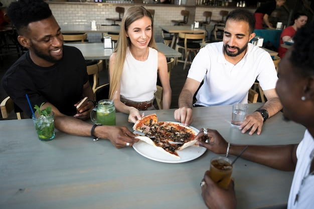 Groep gelukkige mensen die pizza eten Gratis Foto