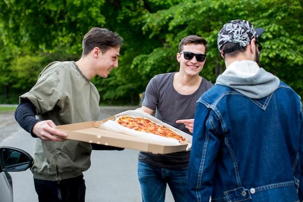 Groep gelukkige mensen die pizza in aard gaan eten Gratis Foto