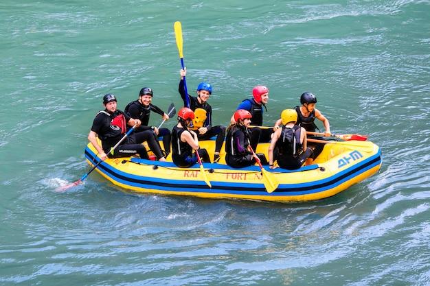 Groep gelukkige mensen met gids whitewater die en op rivier raften roeien. Premium Foto