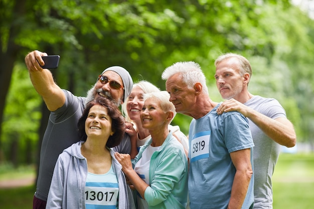 Groep gelukkige senior vrienden die deelnemen aan de zomer marathon race staan samen in bospark nemen selfie groepsfoto Premium Foto