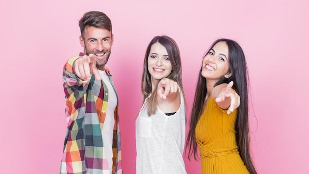 Groep gelukkige vrienden die hun vingers op roze achtergrond richten Gratis Foto