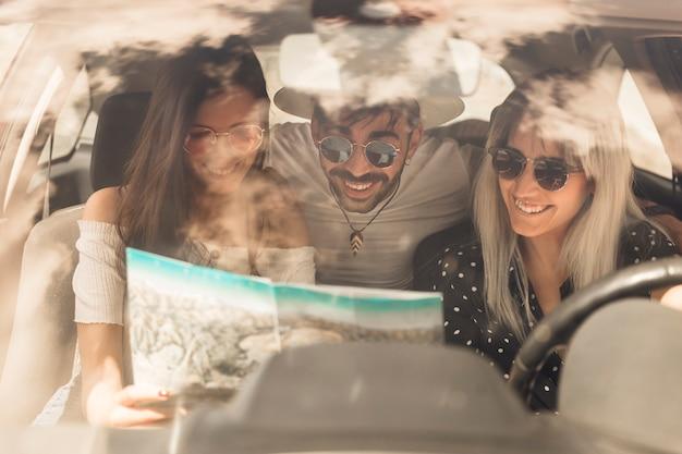 Groep gelukkige vrienden die kaartzitting binnen de auto bekijken Gratis Foto