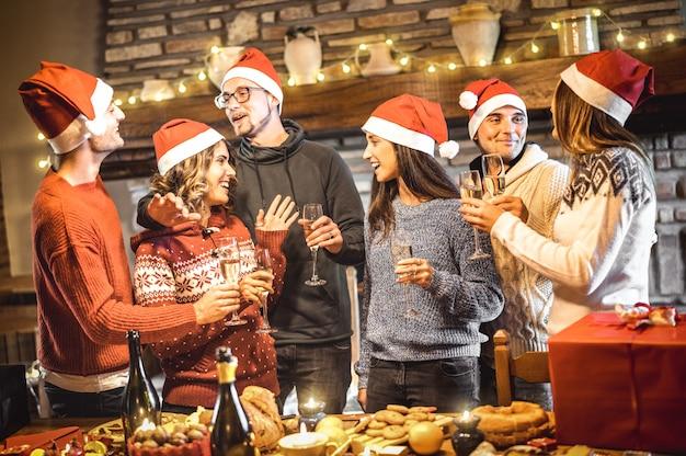 Groep gelukkige vrienden die op santahoeden kerstmis met wijn en zoet voedsel vieren bij dinerpartij Premium Foto