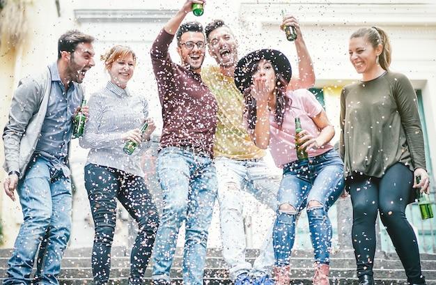 Groep gelukkige vrienden die partij het drinken bier doen en confettien werpen Premium Foto