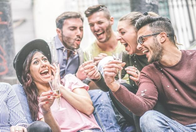 Groep gelukkige vrienden die partij het drinken champagne maken terwijl het werpen van confettien openlucht Premium Foto