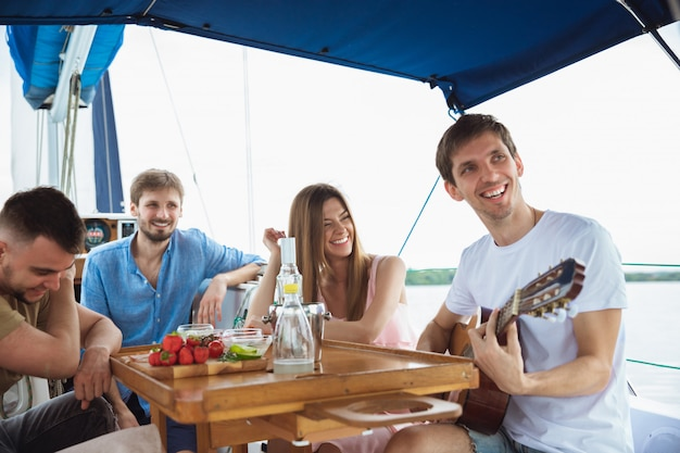 Groep gelukkige vrienden die wodkacocktails drinken en gitaar in een boot spelen Gratis Foto