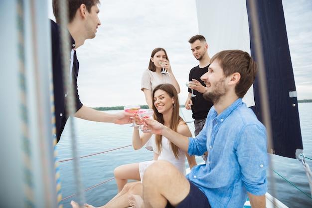 Groep gelukkige vrienden die wodkacocktails in een boot drinken Gratis Foto