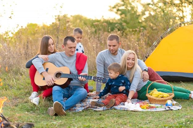 Groep gelukkige vrienden met tent en drankjes gitaar spelen op camping Premium Foto
