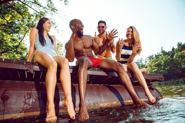 Groep gelukkige vrienden plezier zittend en lachen op de pier op de rivier Gratis Foto