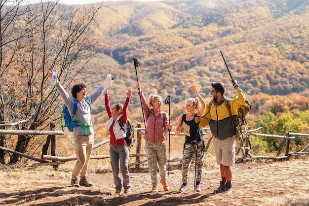 Groep gelukkige wandelaars met handen die omhoog bij open plek stellen. in de achtergrond bergen en bossen. herfst tijd. Premium Foto
